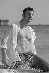All American man with a wet open shirt in the water