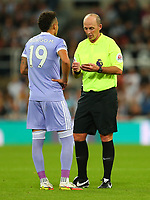 NEWCASTLE UPON TYNE, ENGLAND - SEPTEMBER 17: Rodrigo of Leeds United receives a yellow card from the referee, Mike Dean, during the Premier League match between Newcastle United and Leeds United at St. James Park on September 17, 2021 in Newcastle upon Tyne, England. (Photo by MB Media)