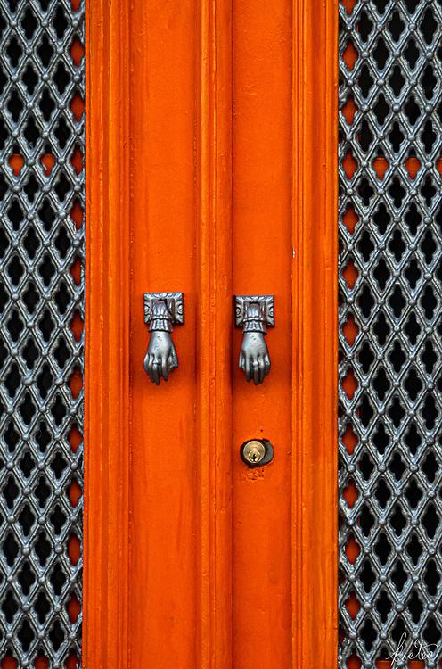 Detail of the Handles of an Orange Doorway in Tavira, Portugal