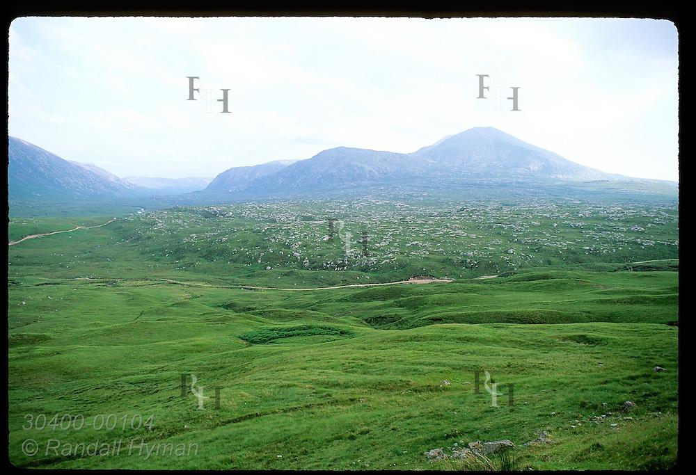 Green plateau is underlain by rocky shield formation in foothills of Scotland's northwest range. Scotland