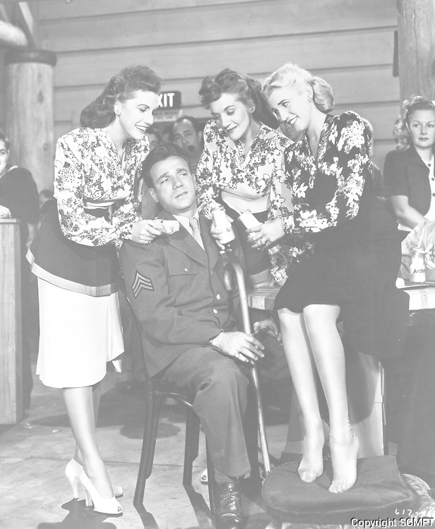 1944 Dane Clark is surrounded by the Andrews Sisters in the film Hollywood Canteen