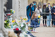 A little girl lays yellow flowers In memory of Prince Philip The Royal Highness the Duke of Edinburgh, London on 9 April 2021.