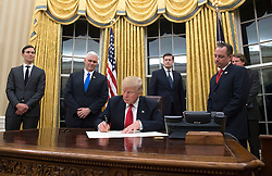 President Donald Trump prepares to sign a confirmation for Homeland Security Secretary James Kelly, in the Oval Office at the White House in Washington, D.C. on January 20, 2017. Photo by Kevin Dietsch/UPI