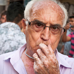 A man blows a whistle to show his support for a protest against increase of the sales tax in Spain to 21%.