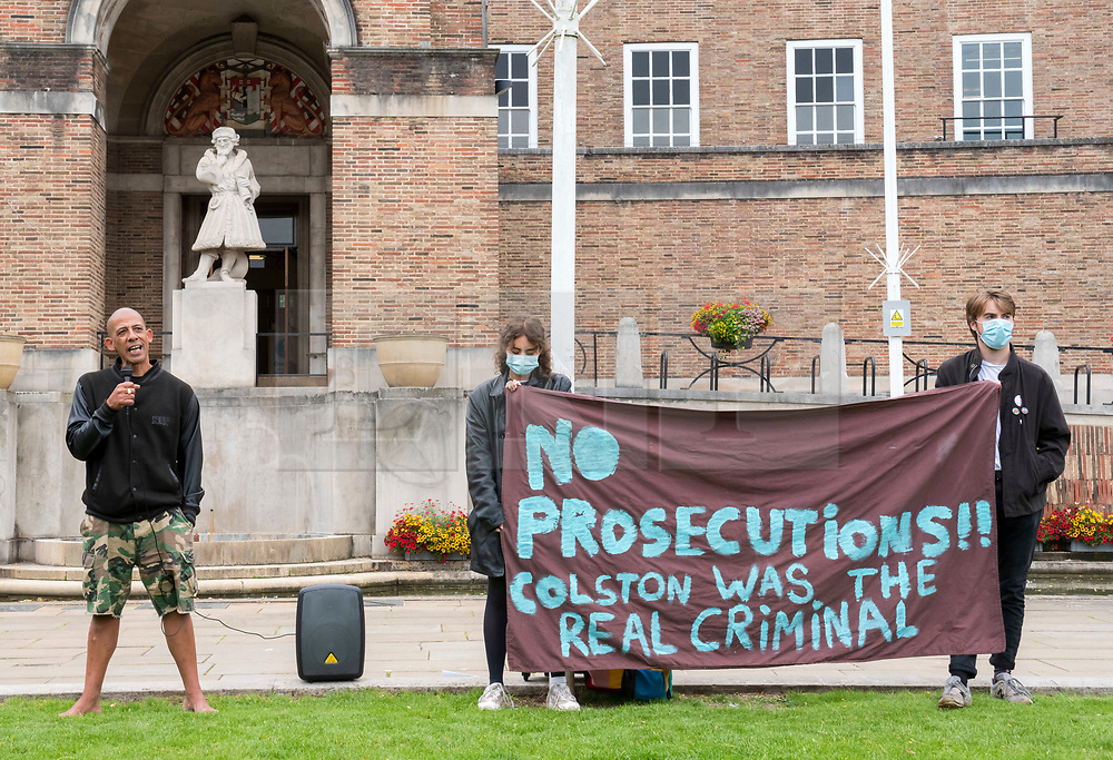 """© Licensed to London News Pictures; 07/07/2020; Bristol, UK. Poet LAWRENCE HOO reads a poem at a protest organised by Stand Up to Racism Bristol for """"No Prosecutions over Colston Statue"""" taking place on College Green in front of City Hall. The protest opposing any prosecutions of people who toppled the statue of Edward Colston and threw it into the water at Bristol Harbourside is taking place just before a Bristol city council meeting where a motion is due for debate calling on the Government to set up a commission to acknowledge, apologise and instigate amends for wrongs that still have an impact today, and asking Labour mayor Marvin Rees to lead the city in lobbying Westminster for an all-party parliamentary inquiry. The motion was tabled by Green Party councillor and former Bristol lord mayor Cleo Lake who was also a founding member of the Countering Colston group, which has campaigned for the city to dismantle its public celebration of slave trader Edward Colston. The statue of Edward Colston was toppled from its plinth and thrown into Bristol Harbour during a Black Lives Matter protest rally and march on 07 June in memory of George Floyd, a black man who was killed on May 25, 2020 in Minneapolis in the US by a white police officer kneeling on his neck for nearly 9 minutes. Police in Bristol are seeking to identify 18 people in connection with what police say is criminal damage to the statue. The killing of George Floyd has seen widespread protests in the US, the UK and other countries, despite the restrictions due to the Covid-19 coronavirus pandemic. Today's event is organised by Stand Up to Racism Bristol and due to the coronavirus pandemic participants are advised of the need to wear masks and maintain social distancing to avoid the spread of the virus. Photo credit: Simon Chapman/LNP."""