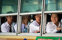 YANGON, MYANMAR - CIRCA DECEMBER 2013: Passengers looking through a bus window in a busy street in Yangon.