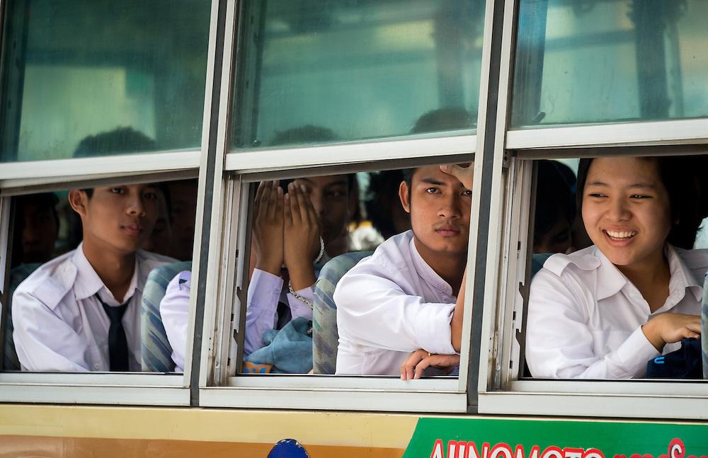 YANGON, MYANMAR - CIRCA DECEMBER 2013: Passengers looking through a bus window in a busy street in Yangon.