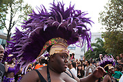 Hackney carnival 2014. The procession started in Ridley Road and passed by the The Hackney Town Hall with thousands of spectators lining the road. A young woman with a purple feather head gear.