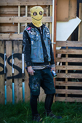 A housing activist wearing a balaclava stands in front of a barricade at the Sweets Way housing estate on 23rd September 2015 in London, United Kingdom. A group of housing activists calling for better social housing provision in London occupied properties on the 142-home estate in Whetstone, in a few cases refurbishing properties intentionally destroyed by the legal owners following eviction of the original residents, in order to try to prevent the eviction of the last resident on the estate and the planned demolition and redevelopment of the entire estate by Barnet Council and Annington Property Ltd.