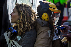 "© Licensed to London News Pictures. 19/11/2016. Heathrow, UK. Protective wear being placed on two female activists, joined by bike locks, before police attempt to cut them apart. A group of activists stage attach themselves to a road surrounding  Heathrow Airport, during a demonstration against the expansion of Heathrow Airport and the building of a third runway. Some activists  threatened ""direct action"". Photo credit: Ben Cawthra/LNP"