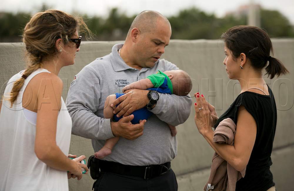 Miami-Dade Fire paramedic Lieutenant Alvaro Tonanez  helps rescue a five-month-old Sebastian de la Cruz who stopped breathing. At right, the baby's aunt, Pamela Rauseo, 37, performed CPR after pulling her SUV over on the side of the road along the west bound lane on Florida state road 836 just east of 57th Avenue around 2:30pm on Thursday, February 20, 2014.  At left is Lucila Godoy who stopped her car to assist with the rescue.