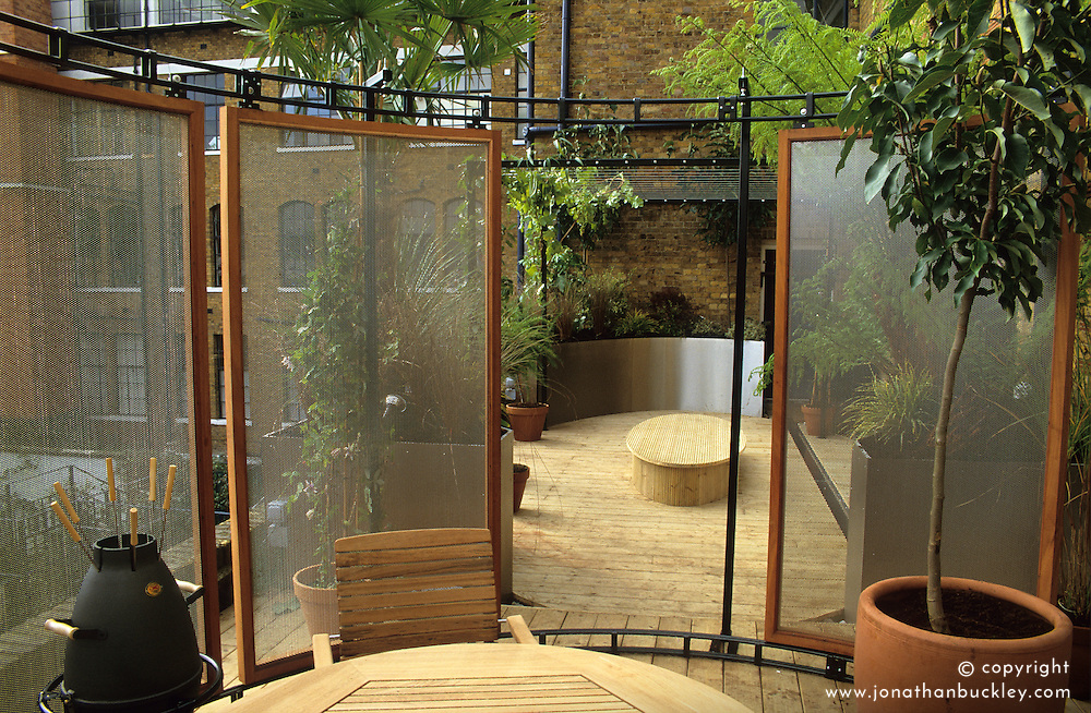 Roof terrace. Dining area with barbecue surrounded by sliding wire mesh screens. Design: Diarmuid Gavin