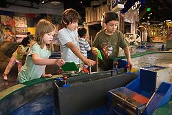 United States, Washington, Bellevue, KidsQuest Children's Museum, boys and girl building dam at Waterways exhibit