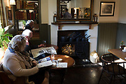 A couple read their Sunday newspapers in a quiet corner of the Pony and Trap pub, October 8th 2017, in Chew Magna, Somerset, England.