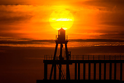 © Licensed to London News Pictures. 31/07/2020. Whitby UK. The sun burns through the light cloud this morning behind Whitby Lighthouse on the Yorkshire coast as the UK faces a heatwave this weekend. Photo credit: Andrew McCaren/LNP