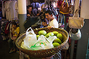 """30 JANUARY 2013 - PHNOM PENH, CAMBODIA:  A vendor sells mangoes from a basket atop his head in the Central Market in Phnom Penh. The Central Market (""""Psah Thom Thmey"""", """"New Grand Market""""), is a large market constructed in 1937 in the shape of a dome with four arms branching out into vast hallways with stalls of goods. It opened in 1937, and was the biggest market in Asia at the time; today it still operates as a market. It was renovated from 2009 to 2011.      PHOTO BY JACK KURTZ"""
