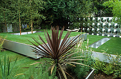 Looking over purple cordyline towards trays of lawn on different levels. Steel rill and birch trees growing through steel hole in lawn. Design Diarmuid Gavin