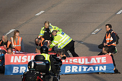 Ockham, UK. 21st September, 2021. Surrey Police officers restrain an Insulate Britain climate activist on the clockwise carriageway of the M25 between Junctions 9 and 10. Activists briefly halted traffic on both carriageways as part of a campaign intended to push the UK government to make significant legislative change to start lowering emissions before being removed and arrested by Surrey Police.