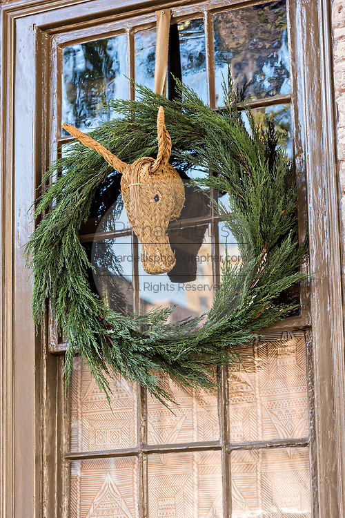 A Christmas wreath hangs from a window on a historic home along Church Street in Charleston, SC.