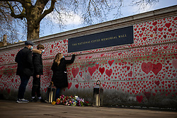 © Licensed to London News Pictures. 08/04/2021. London, UK. A woman adds a name to the National Covid Memorial Wall, which has now been completed with approximately 150,000 hearts painted on the Thames Embankment opposite the Houses of Parliament to remember those who lost their lives to Covid-19. Members of the public are invited to walk the length of the memorial, and campaigners are asking Prime Minister Boris Johnson to make the memorial permanent. Photo credit: Rob Pinney/LNP