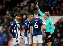 Match referee Graham Scott (right) books West Bromwich Albion's Jake Livermore (second left) during the Premier League match at the Vitality Stadium, Bournemouth.