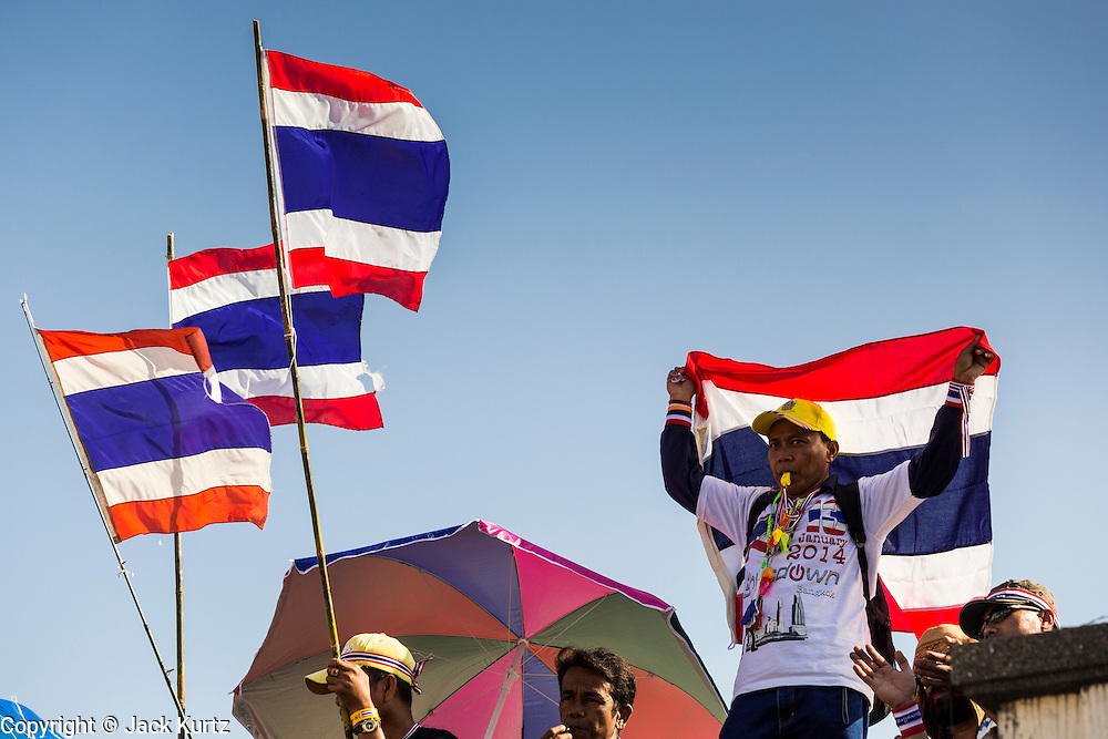 """13 JANUARY 2014 - BANGKOK, THAILAND:  Anti-government protestors wave Thai flags at Victory Monument. Tens of thousands of Thai anti-government protestors took to the streets of Bangkok Monday to shut down the Thai capitol. The protest was called """"Shutdown Bangkok"""" and is expected to last at least a week. The Shutdown Bangkok protest is a continuation of protests that started in early November. There have been shootings almost every night at different protests sites around Bangkok, including two Sunday night, but the protests Monday were peaceful. The malls in Bangkok stayed open Monday but many other businesses closed for the day and mass transit was swamped with both protestors and people who had to use mass transit because the roads were blocked.   PHOTO BY JACK KURTZ"""
