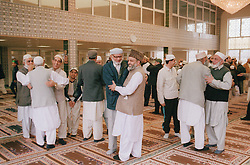 Worshippers inside mosque greeting each other,