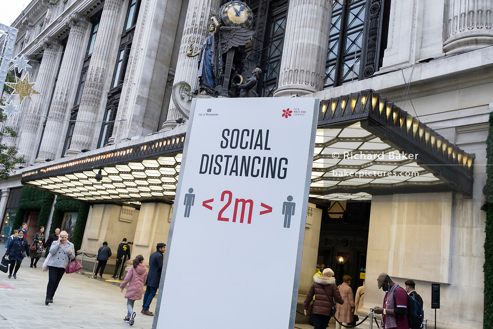 Two-metre social distancing signs advise Oxford Street shoppers to keep apart outside Selfridges, according to government guidelines during the second wave of the UK Coronavirus pandemic, on 30th October 2020, in London, England.