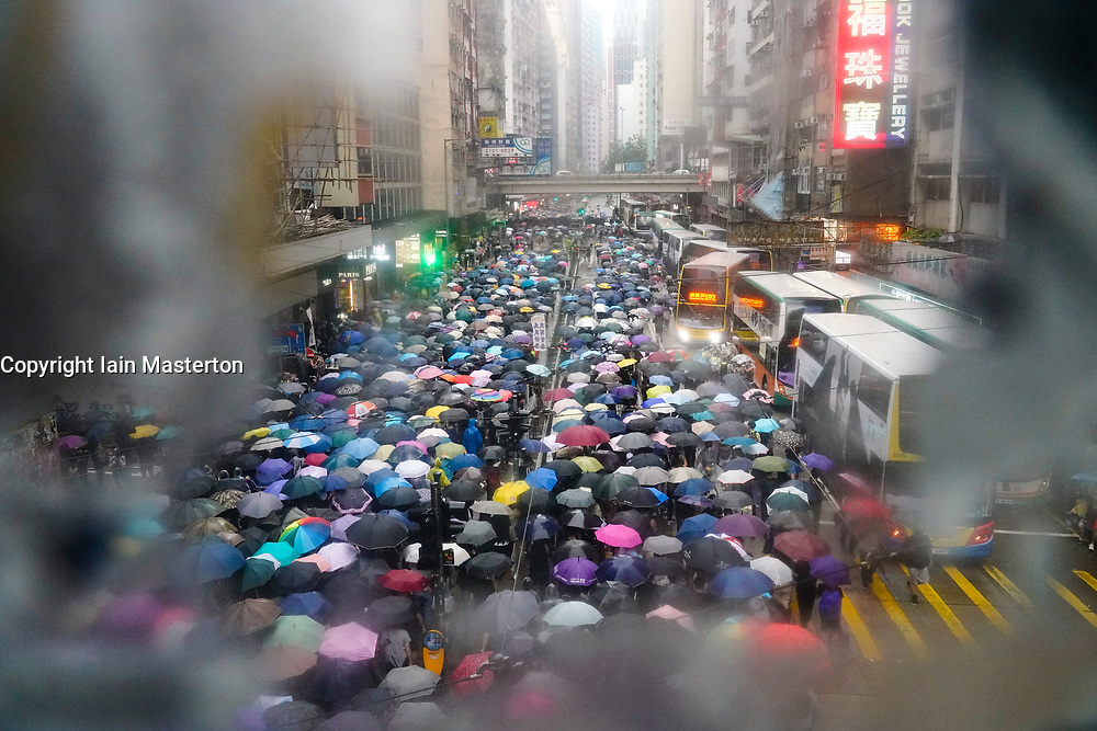 Hong Kong. 6 October 2019. Tens of thousands of pro-democracy protestors march in pouring rain through centre of Hong Kong today from Causeway Bay to Central. Peaceful march later turned violent as a hard-core of protestors confronted police. Pic; Marchers seen through bridge window covered in posters. Iain Masterton/Alamy Live News.