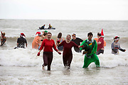 Participants dressed up for Folkestone Lions Club Boxing Day Dip.  An annual fancy dress fundraising event, where all sorts of amusing costumes and characters enter the cold sea of the English Channel at Sunny Sands, Folkestone. UK.