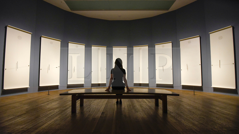 """© Licensed to London News Pictures. 02/07/2019. LONDON, UK.  A staff member views """"Musicals"""", 1985-2004, by Takis.  Preview of a new display by the Greek sculptor Takis at Tate Modern.  The retrospective features over 80 works in Takis' largest exhibition in the UK to date and combines works involving magnetism, light and sound.  The show runs 3 July to 27 October..  Photo credit: Stephen Chung/LNP"""