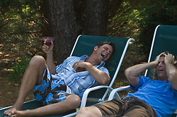 Two Men On Lounge Chairs Laughing
