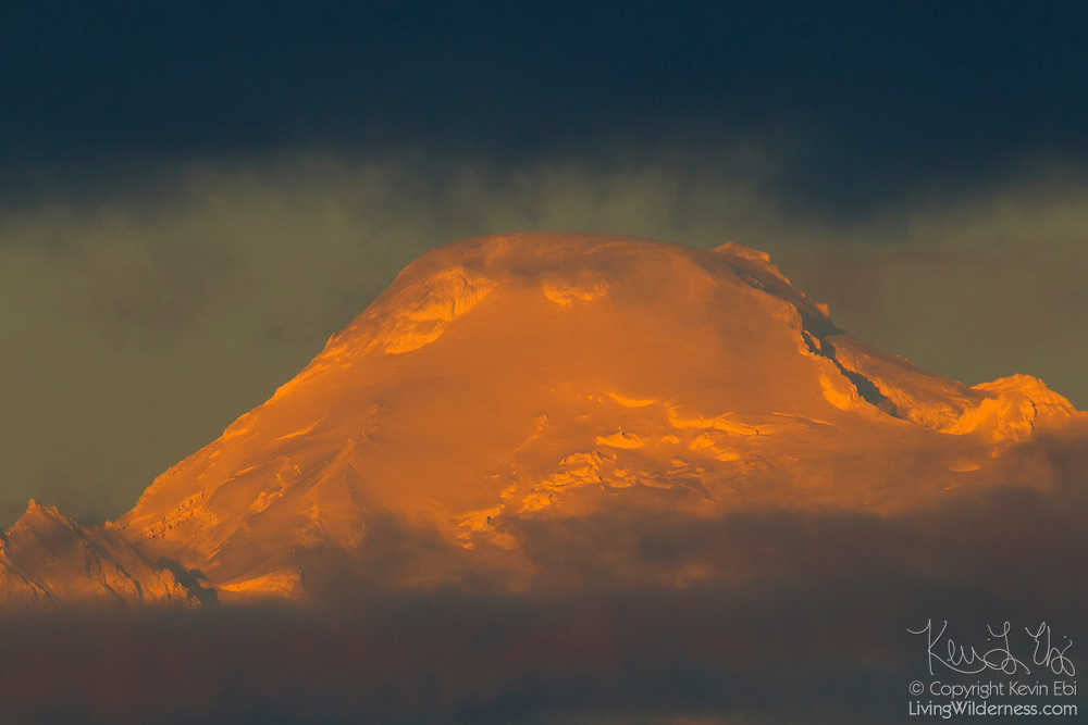 The summit of Mount Baker, a 10,778 foot (3,285 meter) volcano in Whatcom County, Washington, is visible between layers of fog and clouds. Mount Baker is the third highest peak in Washington state.