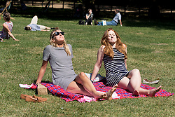 © Licensed to London News Pictures. 12/08/2016. LONDON, UK.  Friends, Leo and Eleanor enjoy a picnic as they sunbathe during the hot and sunny weather today in Green Park in London this lunchtime.  Photo credit: Vickie Flores/LNP
