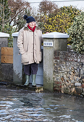 © Licensed to London News Pictures. 03/01/2018. Bosham, UK. A resident looks at tidal flood water coming up the street in Bosham as storm Eleanor hits the south. Winds of up to 80 mph are being forecast today in parts of the UK. Photo credit: Peter Macdiarmid/LNP