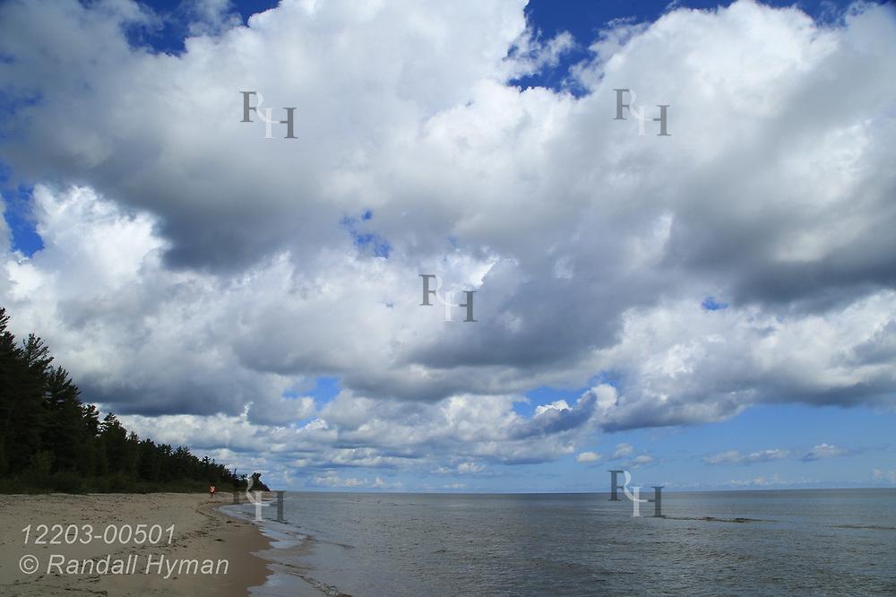 Majestic cumulus clouds tower over sandy beach along Lake Huron on a September morning at Oscoda Roadside Park; Oscoda, Michigan.