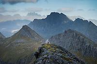 Female hiker ascends rocky ridge towards summit of Markan (602m), Moskenesøy, Lofoten Islands, Norway