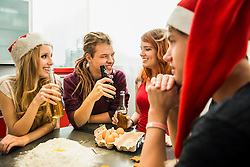 Group of friends preparing cake and drinking beer on Christmas Eve, Munich, Bavaria, Germany