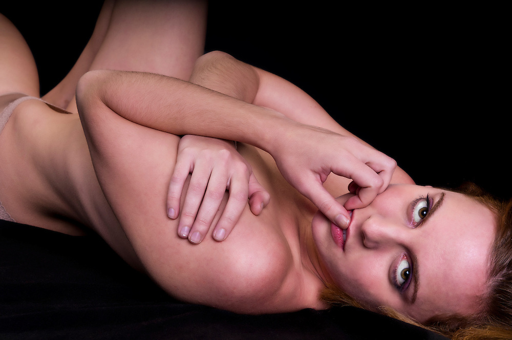 Portrait of sensual woman laying in bed looking at camera.