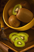 Kiwis in a yellow bowl with some slices in front, on bark with  bamboo like matt background