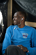 Calais August 2015 The Jungle, camp of migrants, most of whom are trying to get to England. A seventeen year old Sudanese boy listens to music on his phone.