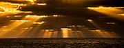 God beams, crepuscular rays of light break through clouds at sunset, calm Southern Ocean, near Macquarie subantarctic Island.