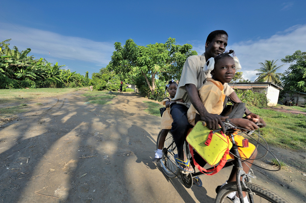 A father takes his daughters to school on his bicycle in the Haitian village of Vaudreuil.