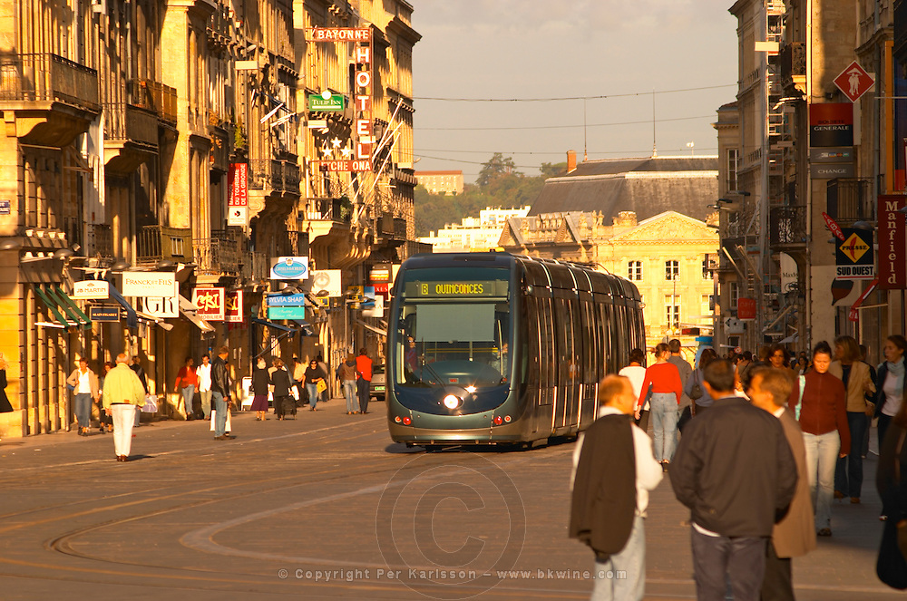 The new modern tram on the posh shopping street Cours de l'Intendence in Bordeaux in evening sun with people walking on the street