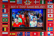 "The Portuguese and Spanish football teams are shown on a street TV screen bordered by international flags before their game in the 2018 World Cup in Russia, in the Slovenian capital, Ljubljana, on 25th June 2018, in Ljubljana, Slovenia. Above the screen it reads: ""Just like in the living room just better."""