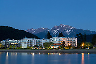 Waterfront condos with Mount Cheam in the background in the early evening.  Photographed from the edge of Harrison Lagoon at Harrison Hot Springs, British Columbia, Canada.  The mountain peaks (from R to L) are Cheam, Lady, Knight, Stewart, and Welch.