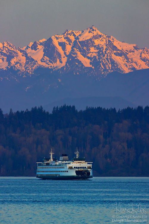 A Washington state ferry (the Puyallup) crosses Puget Sound as Mount Constance stands tall in the background in this view from the Edmonds, Washington, waterfront. Mount Constance, at 7,743 feet (2,360 meters), is one of the tallest peaks in the Olympic Mountains.