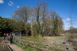 Denham, UK. 6th April, 2021. HS2 security guards and enforcement agents fence off an area during tree felling in Denham Country Park for electricity pylon relocation works connected to the HS2 high-speed rail link. Thousands of trees have already been felled in the Colne Valley where HS2 works will include the construction of a Colne Valley Viaduct across lakes and waterways and electricity pylon relocation.