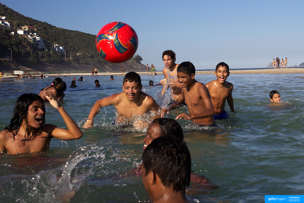 Local youngsters play in the water pools on Sao Conrado beach, Rio de Janeiro,  Brazil. 7th July 2010. Photo Tim Clayton..The beaches of Rio de Janeiro, provide the ultimate playground for locals and tourists alike. Beach activity is in abundance as beach volley ball, football and a hybrid of the two, foot volley, are played day and night along the length and breadth of Rio's beaches. .Volleyball nets and football posts stretch along the cities coastline and are a hive of activity particularly at it's most famous beaches Copacabana and Ipanema. .The warm waters of the Atlantic Ocean provide the ideal conditions for a variety of water sports. Walkways along the edge of the beaches along with exercise stations and cycleways encourage sporting activity, even an outdoor gym is available at the Parque Do Arpoador overlooking the ocean. .On Sunday's the main roads along the beaches of Copacabana, Leblon and Ipanema are closed to traffic bringing out thousands of people of all ages to walk, run, jog, ride, skateboard and cycle more than 10 km of beachside roadway. .This sports mad city is about to become a worldwide sporting focus as they play host to the world's biggest sporting events with Brazil hosting the next Fifa World Cup in 2014 and Rio de Janeiro hosting the Olympic Games in 2016...