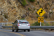 Car and speed saftey warning sign on curve along Highway One 1Big Sur Coast, Monterey County, California